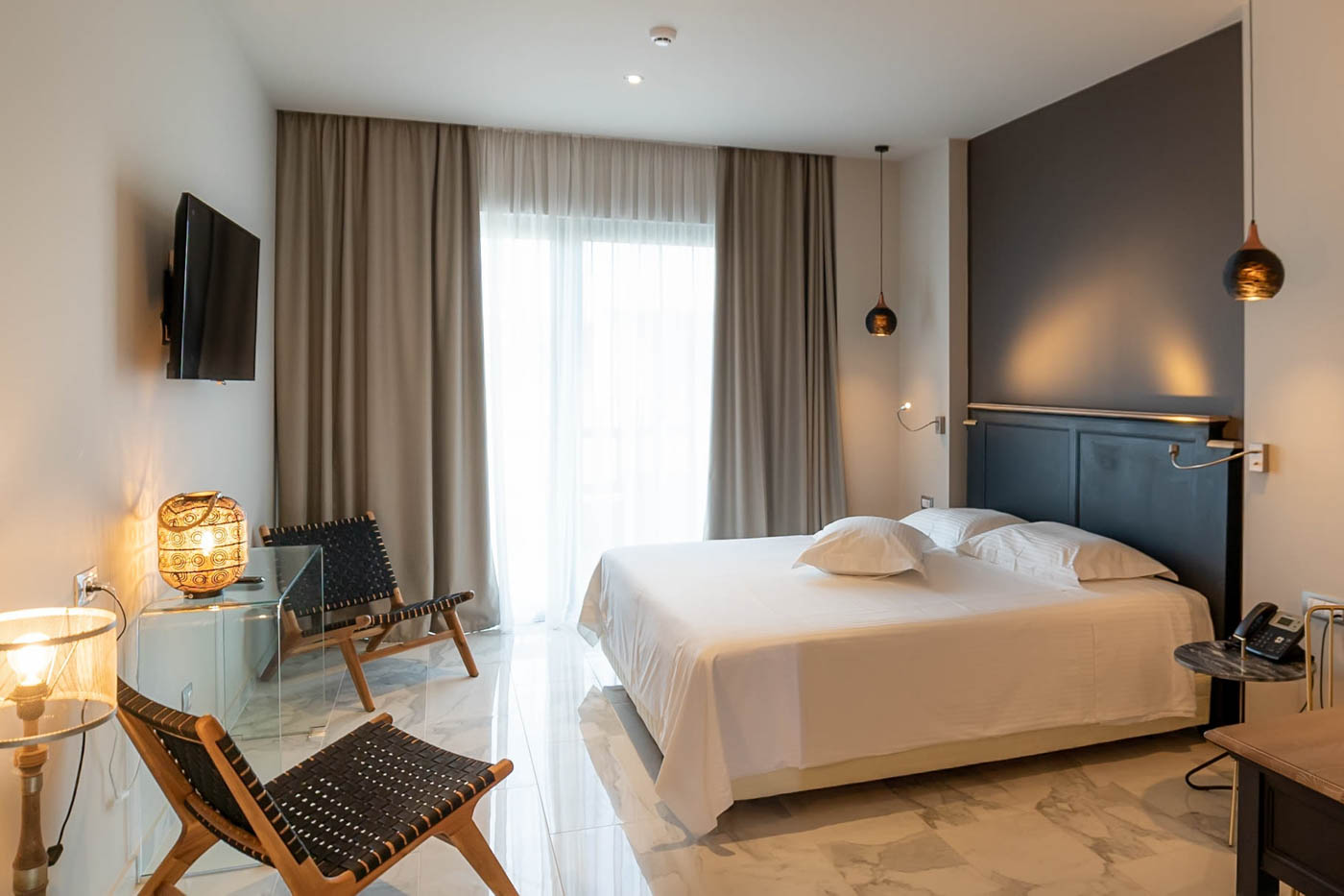 Elysian luxury hotel and spa Kalamata deluxe suite bedroom with a balcony view